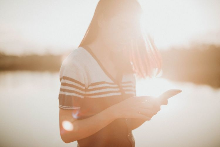 Woman Using Phone By Lake During Sunny Day