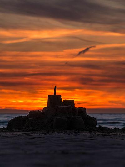 Silhouette rocks on beach against sky during sunset