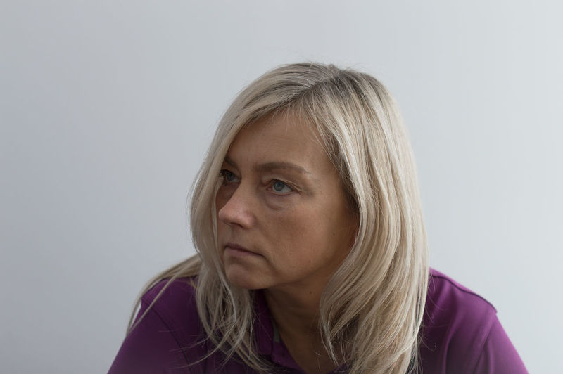 Close-Up Of Woman Looking Away Against White Background