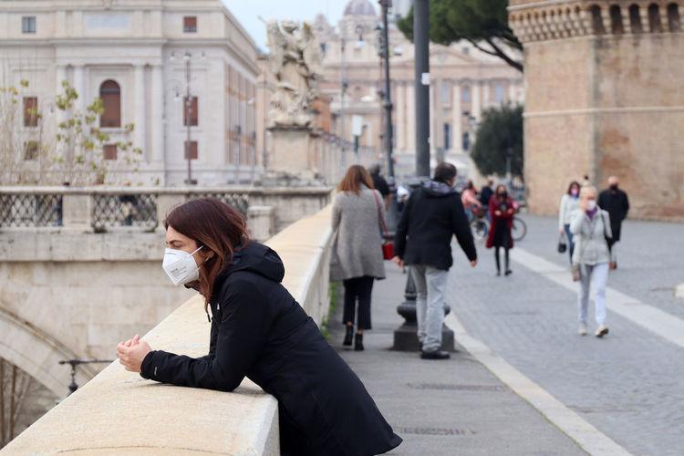 People sitting on street against buildings in city