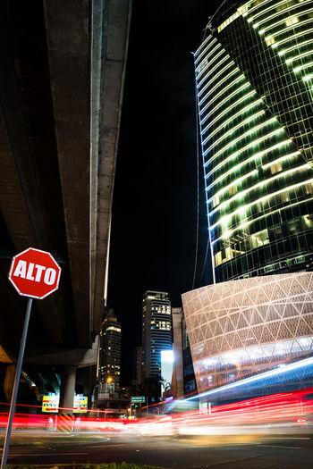 Architecture Car Trails City City Life Cityscape Illuminated Long Exposure Neon Night No People Skyscraper Stop Sign Urban Skyline