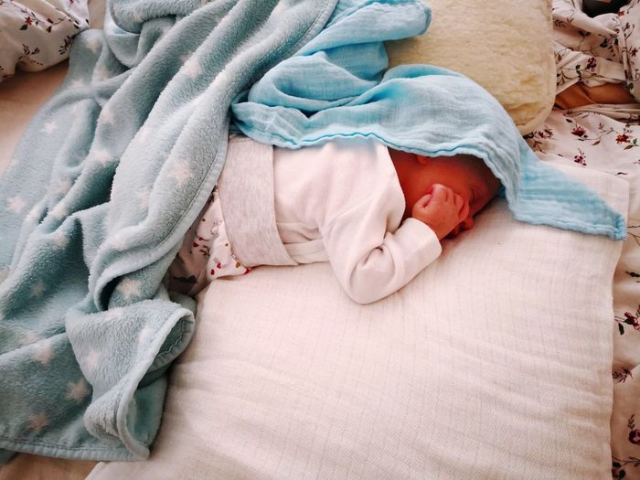 High angle view of cute baby boy sleeping on bed at home