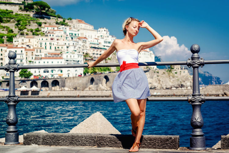 Beautiful young woman posing in Atrani town in Amalfi coast. Italy Amalfi Coast Atrani Blonde Holiday Mediterranean Sea Slim Summer Dress Summertime Vacations Woman Beautiful Woman Built Structure Full Length Italy Landscape Outdoors Railing Standing Summer Sunny Day Tourist Resort Urban Landscape Urban Skyline Young Adult Young Women