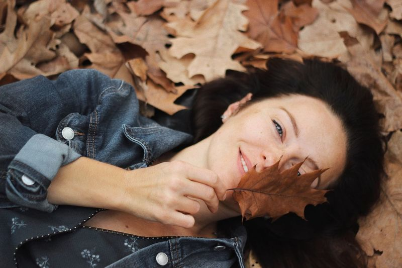 Portrait of young woman lying down on leaves during autumn