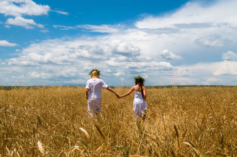 Rear view of mother and daughter walking on field against sky