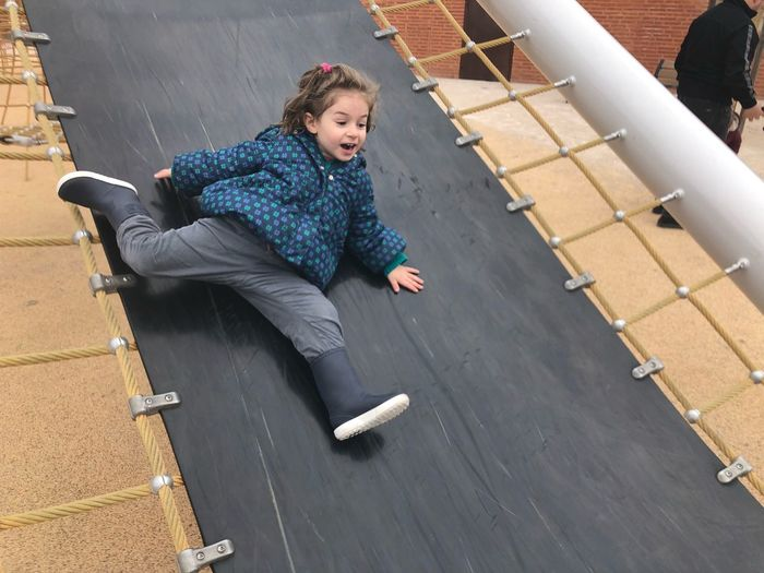 High Angle View Of Girl Sliding On Slide At Playground