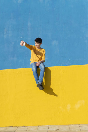 Full length of boy using phone while sitting against wall