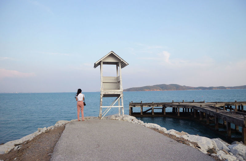 Rear view of woman standing by lifeguard hut and sea against sky