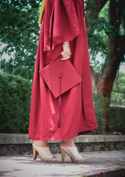 Low Section Of Woman Wearing Graduation Gown Holding Mortarboard