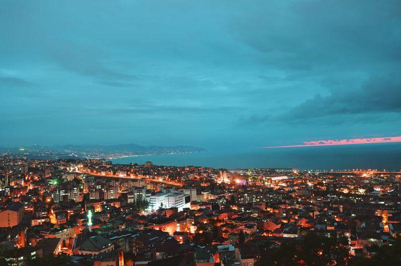 High angle shot of illuminated cityscape against sky at dusk