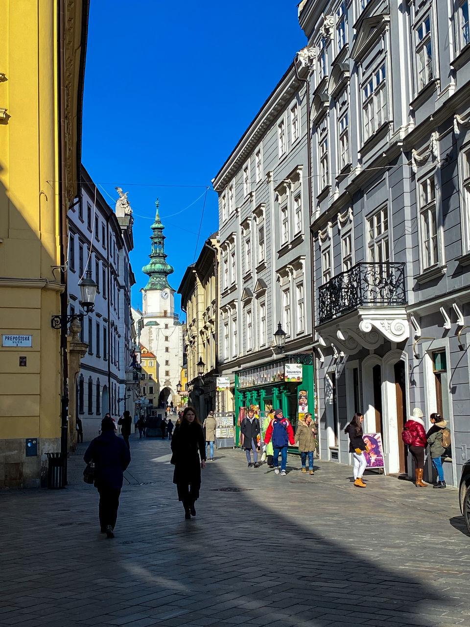PEOPLE WALKING ON STREET AMIDST BUILDINGS IN CITY AGAINST CLEAR SKY