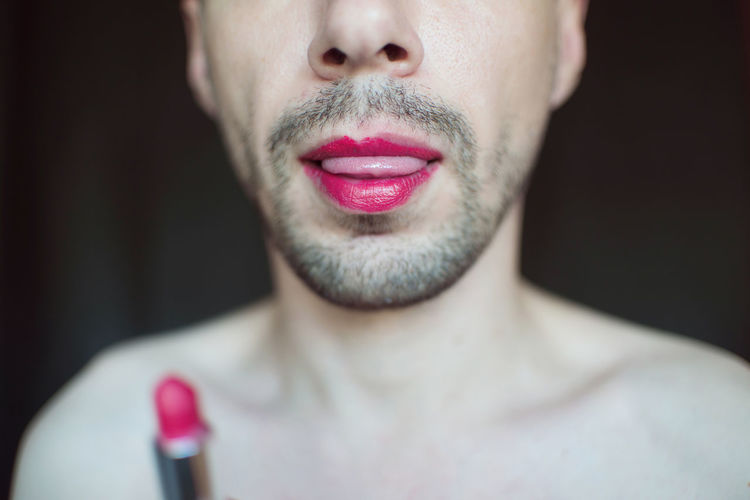 Midsection of transgender man with red lipstick against black background
