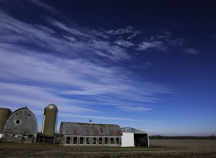 Abandoned building in field against sky