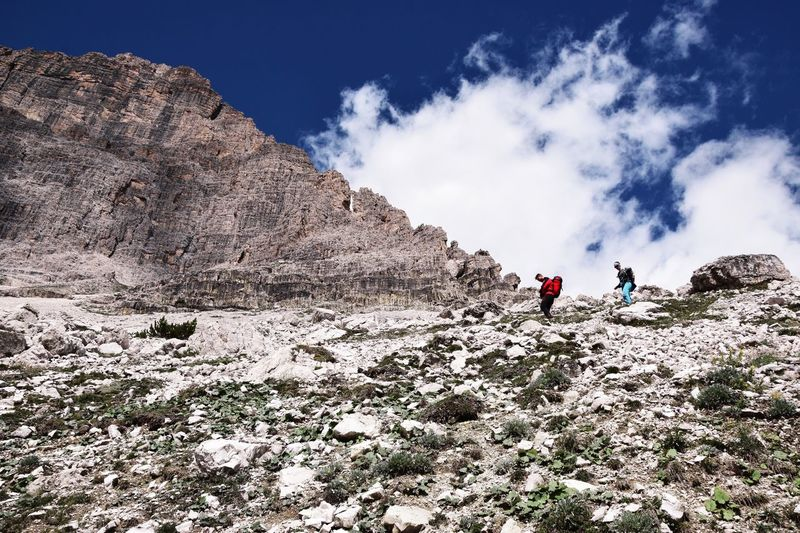 Low Angle View Of Hikers Hiking On Mountain