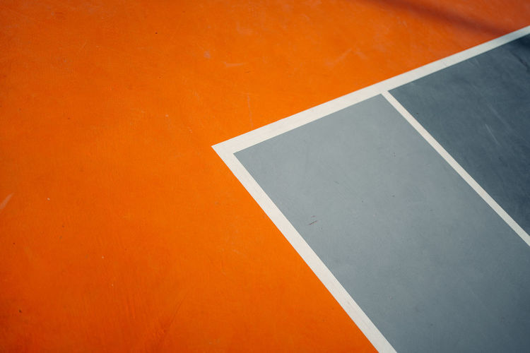 High angle view of empty chair against orange wall