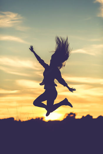 Silhouette of a woman jumping in the sunset Field Free Freedom Happy Sunlight Woman Day Energetic Flying Full Length Jumping Mid-air Motion Nature One Person Outdoors People Real People Silhouette Sky Sunset Vertical