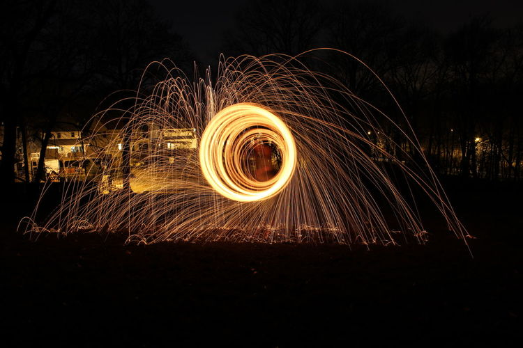 Blur Image Of Person Spinning Wire Wool On Field At Night