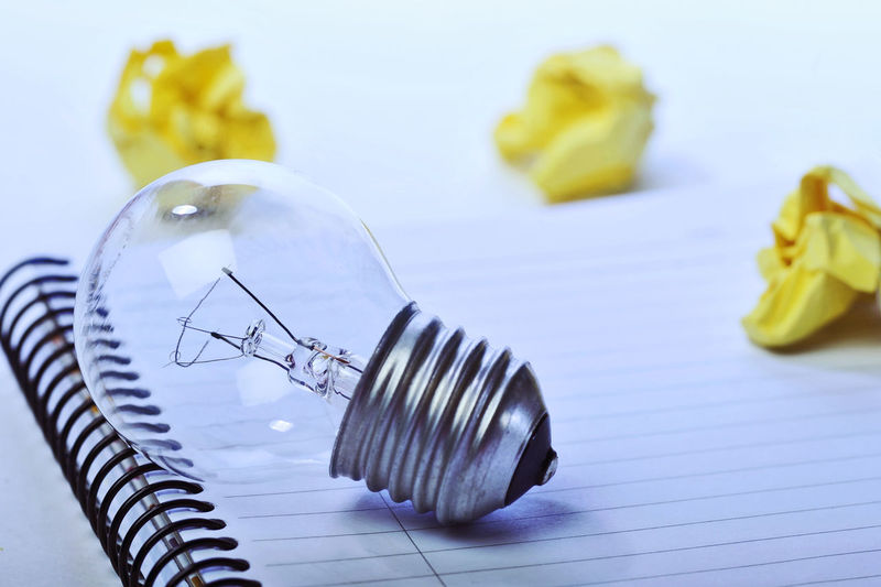 Close-up of light bulb and crumpled paper on spiral notebook