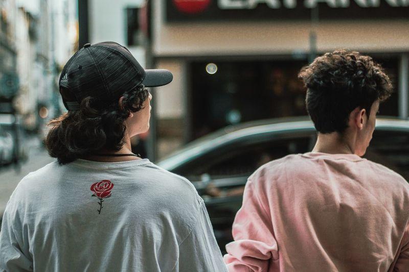 Rear view of friends on street in city