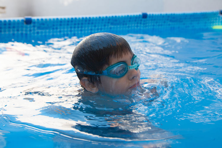 Portrait of boy swimming in pool