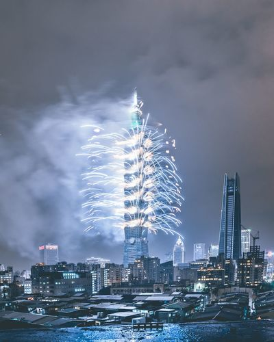Building Exterior Architecture Skyscraper City Built Structure Firework Display Night Sky Cityscape Illuminated Celebration Firework - Man Made Object Urban Skyline Long Exposure Water Tower Exploding Cloud - Sky Blurred Motion Travel Destinations