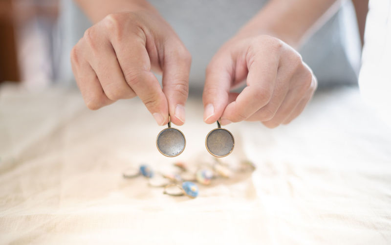 The female hands holding and choosing the wood plate frame earring for embroidery thread.