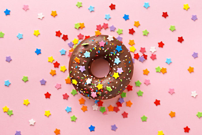 Donut decorated with sweet stars on a pink background. Celebration concept. Top view Candy Celebration Dessert Donut Food Freshness Glazed Food Indulgence Multi Colored No People Party Ready-to-eat Sprinkles Sweet Food Temptation Unhealthy Eating