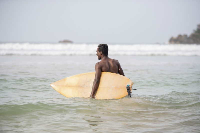 Rear view of shirtless male surfer carrying surfboard in sea