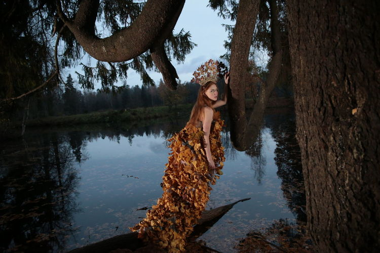 Portrait of woman wearing dress made of autumn leaves while standing against lake at dusk