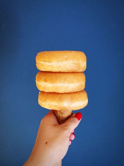 Cropped image of woman holding donuts with ice cream cone against blue background