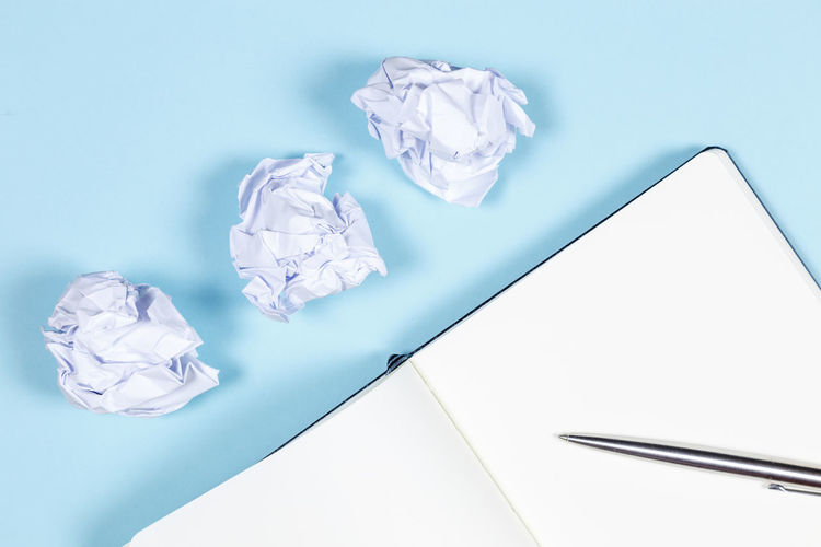 Paper Crumpled Crumpled Paper Indoors  Crumpled Paper Ball No People High Angle View Studio Shot Blue Still Life Table Copy Space Garbage Frustration White Color Close-up Negative Emotion Emotion Blue Background