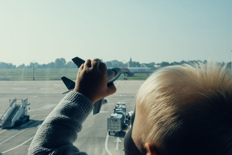 Close-up of boy holding toy airplane on glass window at airport