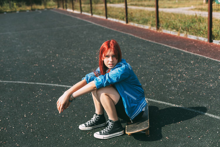 Cute teen girl sitting on a skateboard in the afternoon, outdoors