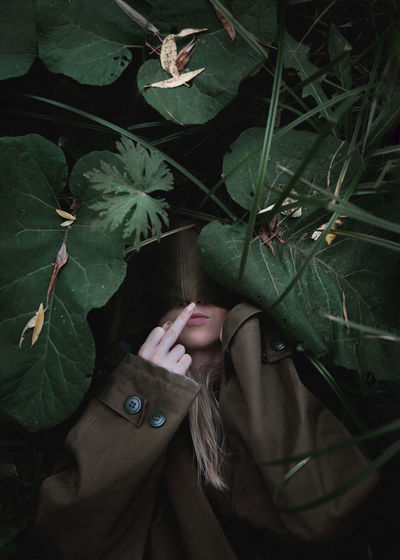 A woman lies in the tall grass and shows the middle finger