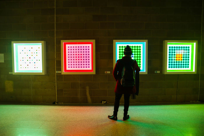 """A man is standing in front of the artwork of Neil Shirreff, """"Light movements"""". 2016 Adult Canary Wharf Canary Wharf Winter Lights Free Illuminated Indoors  Interactive Art Light Installation Light Movement Light Movements London Long Exposure Love Motion Multi Colored Neil Shirreff Observing One Person Optical Illusions Overexposed Perception Photograms Standing Window Gallery Canary Wharf"""