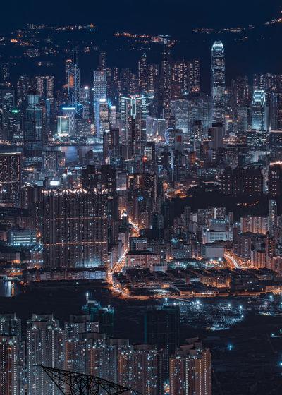 Digital composite image of illuminated cityscape against sky at night in kowloon peak