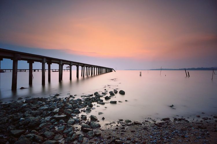 EyeEm Selects Sunset Horizon Over Water Scenics Reflection Sky Tranquility Tranquil Scene Beach Sea Idyllic Cloud - Sky Bridge - Man Made Structure Water Outdoors Sunlight Travel Destinations Landscape No People Blue Beauty In Nature