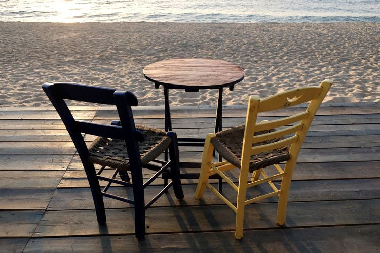 Empty chairs and table at beach
