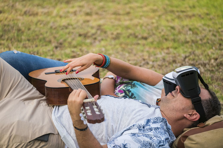 Man and woman wearing virtual reality simulator while playing guitar