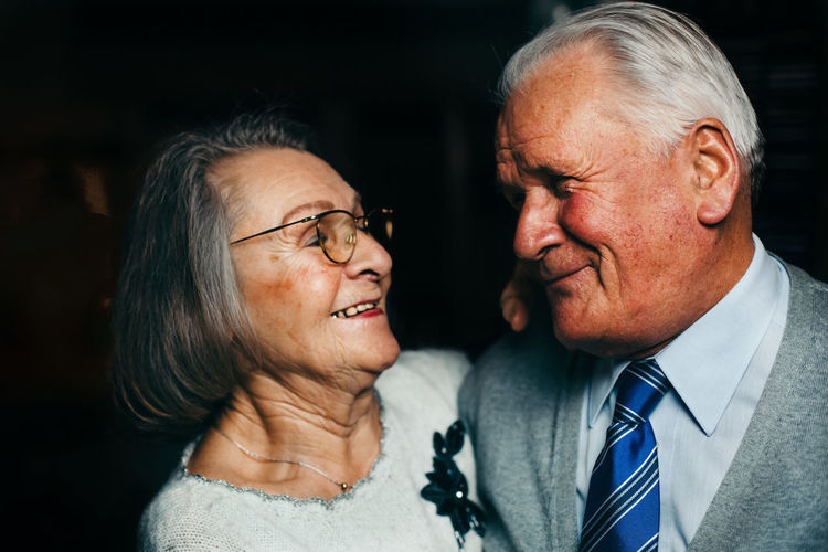 Happy senior couple looking at each other Adult Black Background Bonding Close-up Couple - Relationship Eyeglasses  Happiness Husband Indoors  Love Married Men Night People Real People Retirement Senior Adult Senior Couple Senior Men Senior Women Smiling Togetherness Two People Wife Young Adult