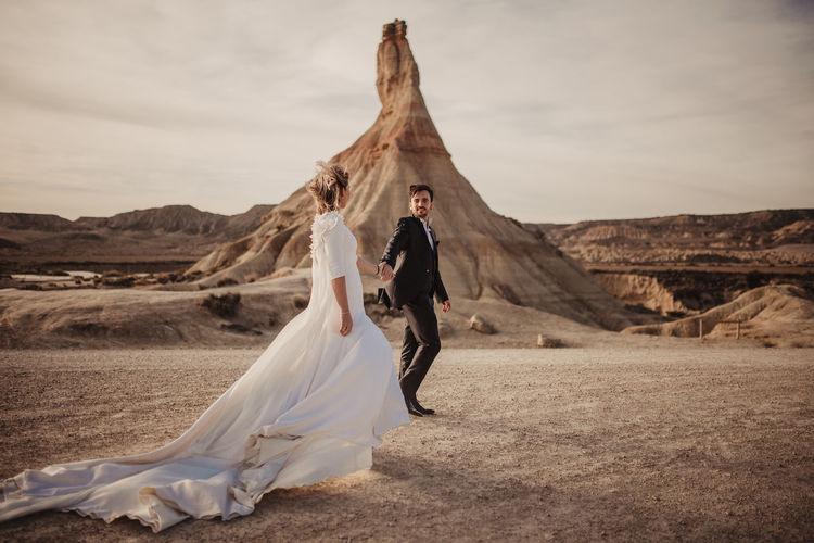 Woman with umbrella standing on desert