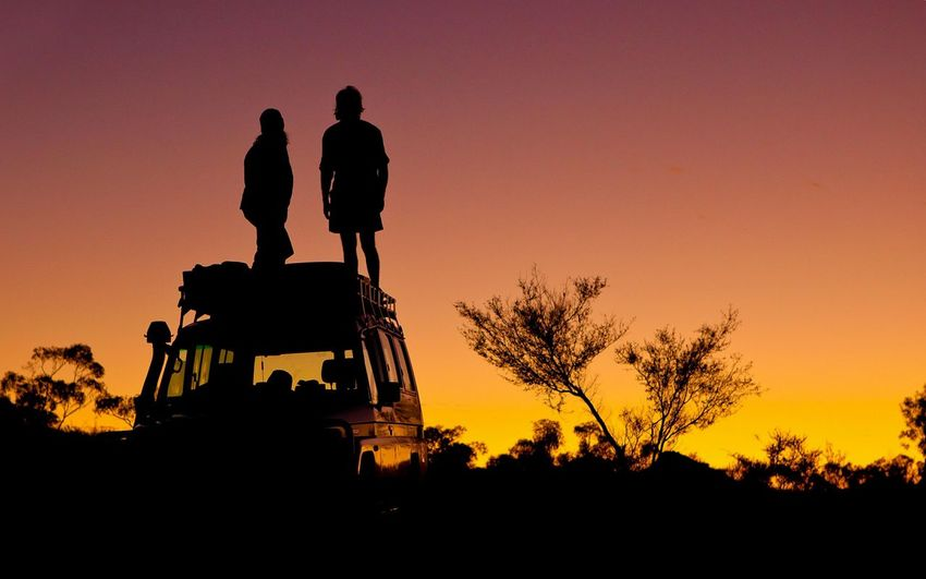 Silhouette people standing on car roof against sky