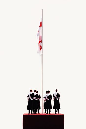 People standing in front of flag against white background