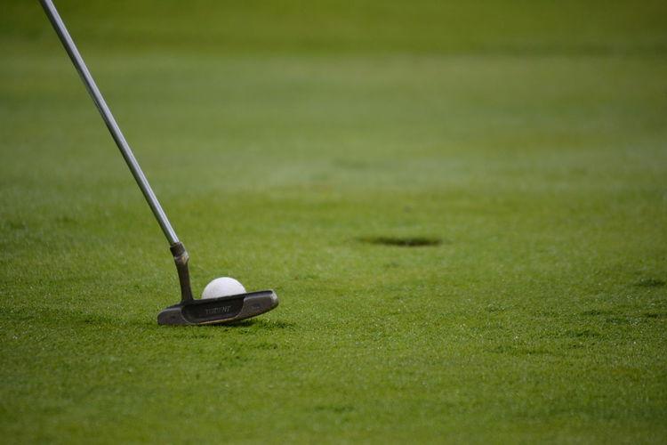 Golf club putting ball in hole