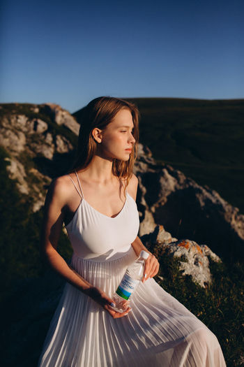 Young woman looking away while standing on rock against sky