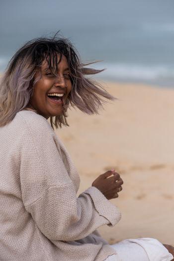 Happy woman sitting on beach