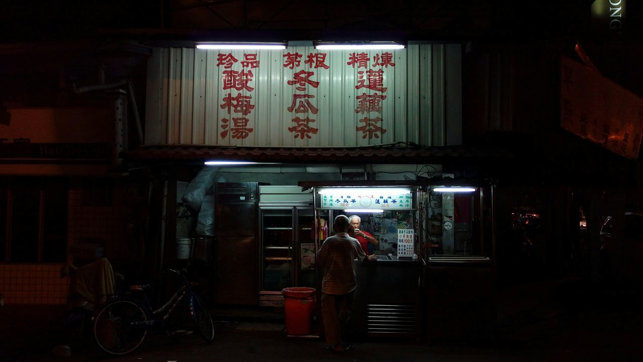 WOMAN STANDING AT NIGHT
