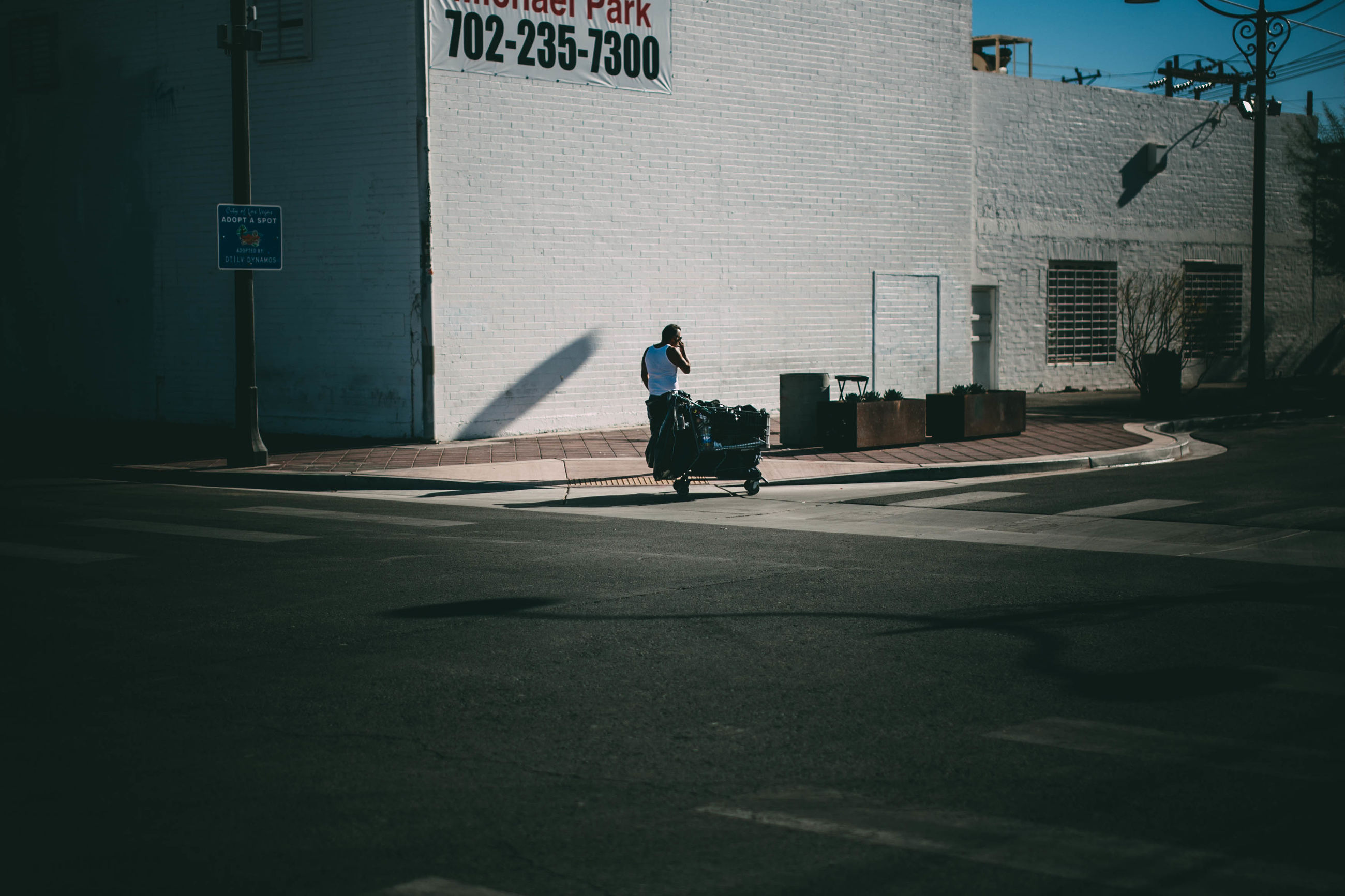 building exterior, built structure, transportation, architecture, scooter, sunlight, street, day, outdoors, men, land vehicle, city, one person, shadow, real people, full length, people