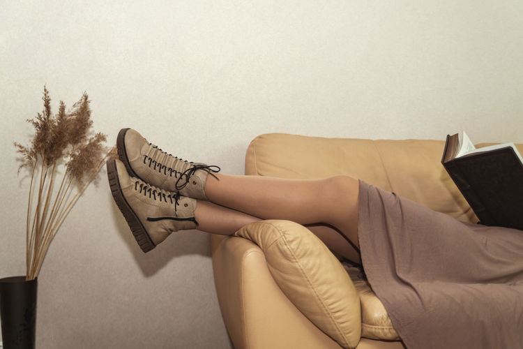 Low section of woman sitting on sofa