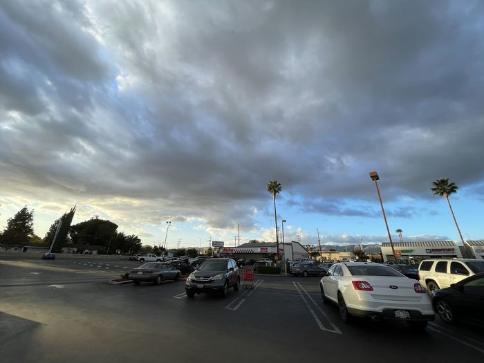 Vehicles on road in city against cloudy sky